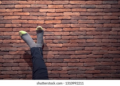 Feet and socks resting on a red brick wall