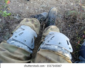 Feet of a special forces soldier during a vacation. Boots and knee pads are badly worn and damaged. After battle.