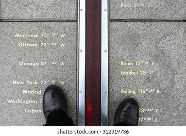 Feet stand on opposite sides of the Prime Meridian. Greenwich, London, UK.