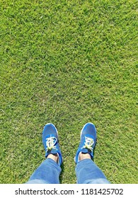 A feet standing on a green grassy turf.