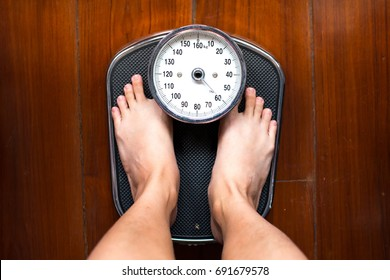 The feet standing on weighing apparatus.