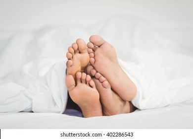 Feet sticking out from the blanket in bedroom