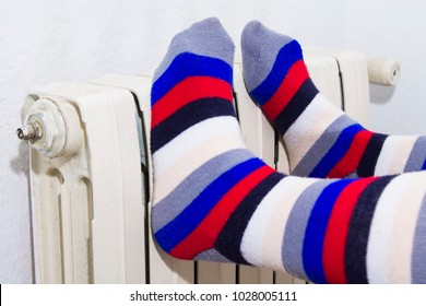 feet with striped socks on radiator