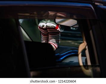 Feet in striped socks propped up on dashboard of car.