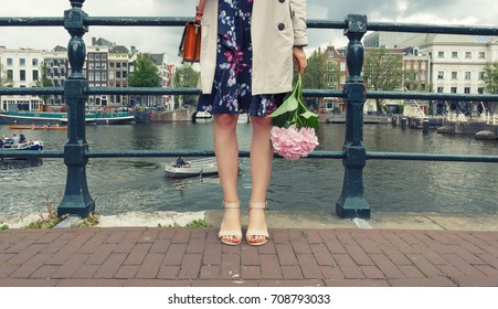 Feet stylish young woman with pink flower on the bridge of Amsterdam.
