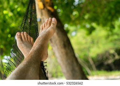 Feet swinging in a hammock. Relaxing on the beach at sunset. Tropical leisure. Feet in the sand after a walk along the beach. Summer time. Uninhabited island and a homemade hammock.