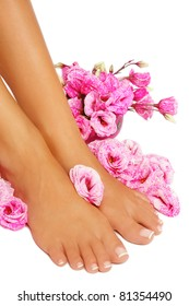Feet of tanned woman with french pedicure and pink flowers around, on white background