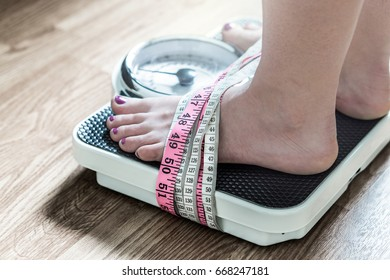 Feet tied up with measuring tape to a weight scale. Addiction and obsession to weight loss. Anorexia and eating disorder concept.