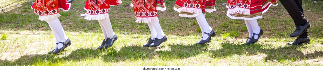 Feet of traditional dancers, panoramic background