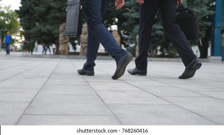 Feet of two businessmen walking in city street. Business men commute to work together. Confident guys being on his way to office. Legs of colleagues going outdoor. Slow motion Close up.