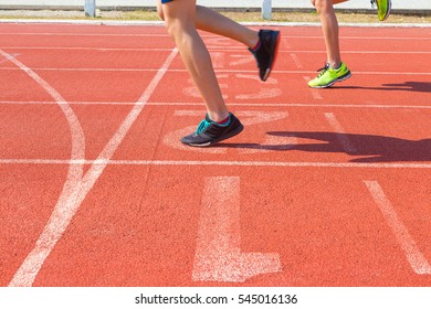 feet of two female runners running on race track at finish line