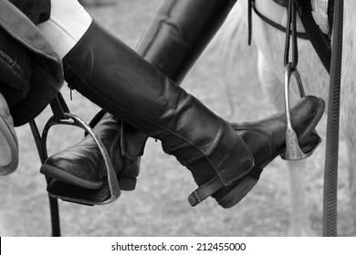 Feet of two pony friends putting their horse riding boots on each others stirrup. Image in black and white with focus on boots.
