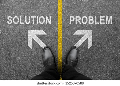 Feet and two white arrows with solution and problem. Top view of businessman on road background from above. A business man in black shoes standing on pathway floor. Successful business idea concept.