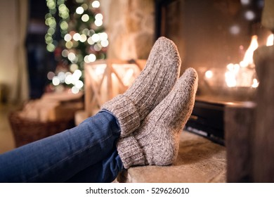 Feet of unrecognizable woman in socks by the Christmas fireplace