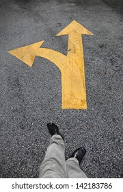 A feet walking towards a yellow traffic arrow signage on an asphalt road indicating a detour left turn.