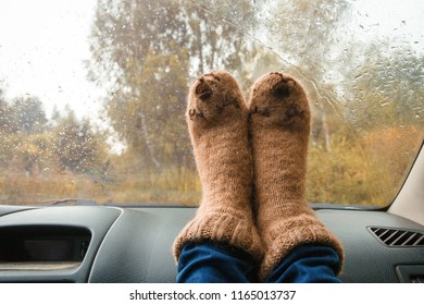 Feet in warm cute socks on car dashboard. Travel, road trip and autumn fall concept.