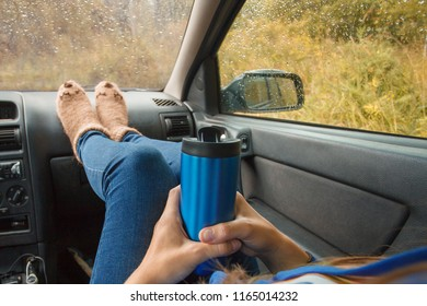Feet in warm cute socks on car dashboard. Travel, road trip and autumn fall concept. Focus on thermos bottle cup with hot drink in female hands. Autumn car trip.