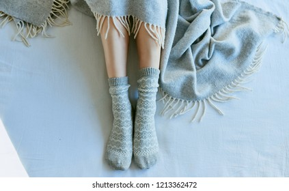 Feet in warm socks peeking out from under the blankets.