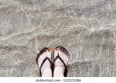 Feet in the water on the sand in flip-flops
