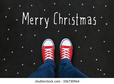 Feet wearing red shoes on black background with Merry Christmas text