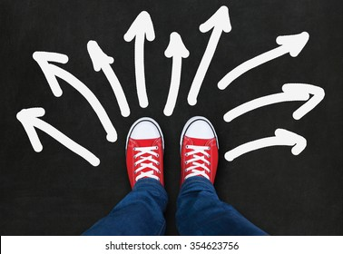 Feet wearing red shoes on black background with arrows in different direction
