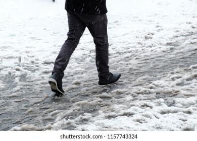 Feet in wet snow on the street, dirty snow, walking through slush