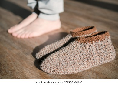 Feet of a woman in funny home made by hand slippers on the wooden warm floor background. Cozy home atmosphere. Warm floor heating concept. Close-up of female legs stepping by hardwood floor at home