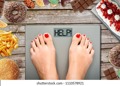Feet of woman on weighting scale asking for help to avoid the temptation to eat unhealthy food