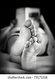 Feet of a woman reading on the bed