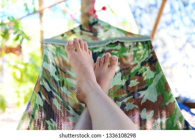 Feet of woman relax on the crib over nature background.