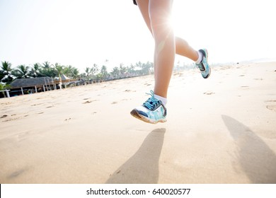 Feet of the woman that is jogging by the sea at the sunrise