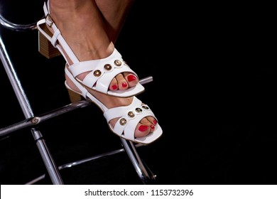 feet of a woman who sits on a bar stool with metal construction in front of black background, she wears white sandals and has red painted toenails
