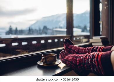 Fühlen Sie sich in Wollsocken an der Alpenübersicht. Die Frau entspannt sich mit einer Tasse heißen Getränk durch die Bergsicht. Nahaufnahme zu Füßen. Konzept der Winter- und Weihnachtsferien.