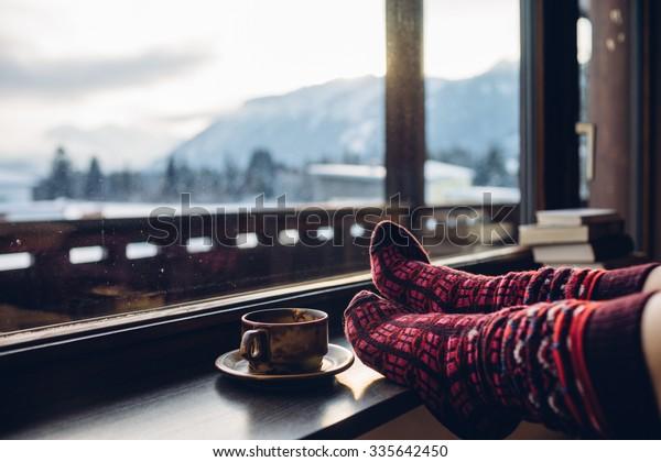Ноги в шерстяных носках у Альп с видом на горы. Женщина расслабляется с видом на горы с чашкой горячего напитка. Встать на ноги. Концепция зимних и рождественских праздников.
