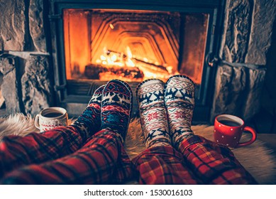 Fühlen Sie sich in Wollsocken am Weihnachtskamin. Das Familiensitzen entspannt sich mit einer gemütlichen, authentischen Feuerstelle mit einer Tasse heißen Getränks und erwärmt die Füße. Konzept der Winter- und Weihnachtsferien
