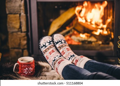 Feet in woollen socks by the Christmas fireplace. Woman relaxes by warm fire with a cup of hot drink and warming up her feet in woollen socks. Close up. Winter and Christmas holidays concept.