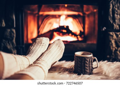 Fühlen Sie sich in Wollsocken am Weihnachtskamin. Die Frau entspannt sich durch warmes Feuer mit einer Tasse heißen Getränken und wärmt sich in Wollsocken die Füße auf. Nahaufnahme zu Füßen. Konzept der Winter- und Weihnachtsferien.