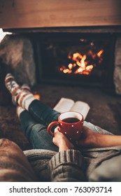 Feet in woollen socks by the Christmas fireplace. Woman relaxes by warm fire with a cup of hot drink and warming up her feet in woollen socks. Cozy atmosphere. Winter and Christmas holidays concept.