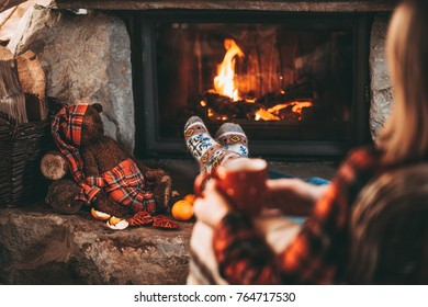 Feet in woollen socks by the Christmas fireplace. Woman relaxes by warm fire with a cup of hot drink and her Teddy Bear friend toy. Close up. Winter and Christmas holidays concept.