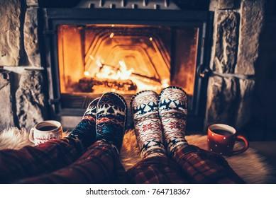 Fühlen Sie sich in Wollsocken am Weihnachtskamin. Ein Paar sitzt unter der Decke, entspannt sich durch warmes Feuer und erwärmt sich die Füße in Wollsocken. Konzept der Winter- und Weihnachtsferien.