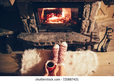 Feet in woollen socks by the cozy Christmas fireplace. Woman relaxes by warm fire with a cup of hot drink and warming up her feet in woollen socks. Winter and Christmas holidays concept.
