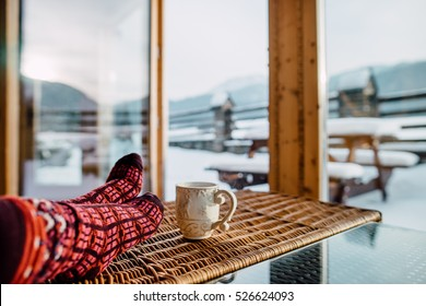 Feet in woollen socks by the Tatra mountains view. Woman relaxes by mountain view with a cup of hot drink in cosy chalet house. Close up on feet. Winter and Christmas holidays concept