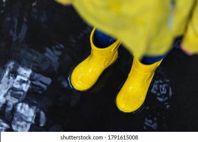 Feet in yellow rubber boots standing in a puddle, copy space