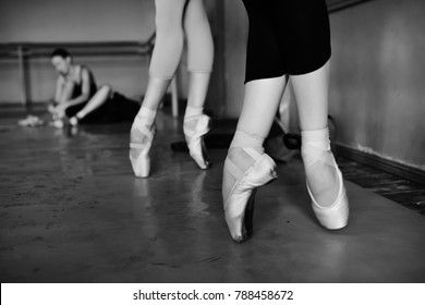 feet of young ballerinas in pointe shoes close-up against the backdrop of a ballet class