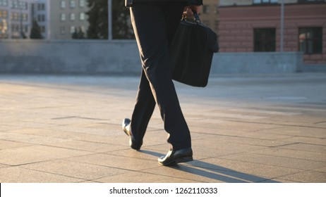 Feet of young businessman with a briefcase walking in city street. Business man commuting to work. Confident guy in suit being on his way to work. Cityscape backround. Slow motion Rear view Close up.