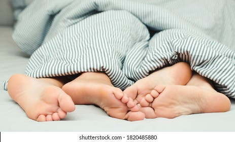 Feet of a young couple lying on the bed at honeymoon. Passionate love. Love lying in bed in hotel. Close up legs under stripes blanket. Sensual and intimate moment of lovers. Morning time together.