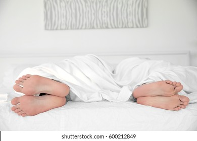 Feet of young cute couple together in bed