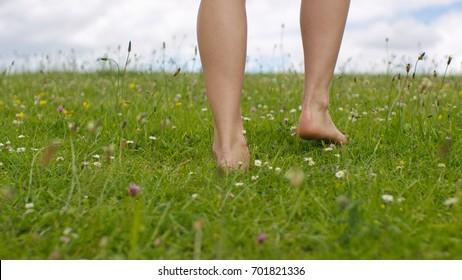 Feet of a young female walking barefoot through green grass