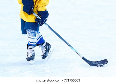 Feet of a young hockey player, hockey stick and puck close-up on the background of the ice. Hockey player leads the puck.