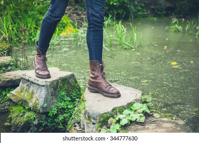 The feet of a young person trekking across stepping stones in a small pond